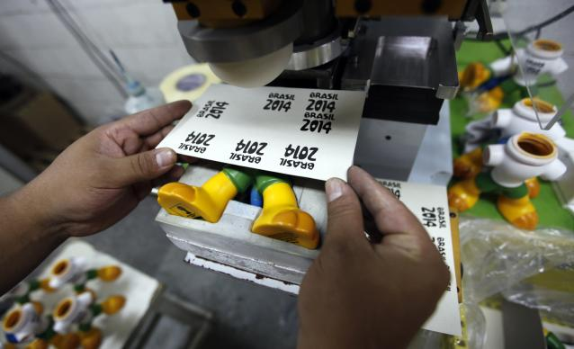 An employee makes toys of Fuleco the Armadillo, the official mascot of the FIFA 2014 World Cup, at a factory in Sao Bernardo do Campo February 27, 2014. The 2014 World Cup will be held in Brazil from June 12 through July 13. REUTERS/Paulo Whitaker (BRAZIL - Tags: SPORT SOCCER BUSINESS WORLD CUP SOCIETY)