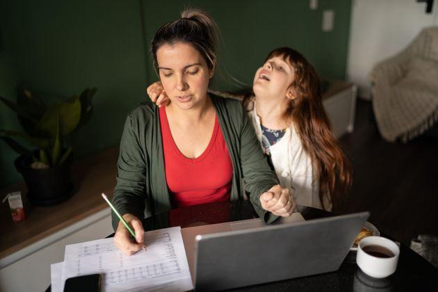 Mid adult woman trying to work with daughter at home (Photo: FG Trade via Getty Images)