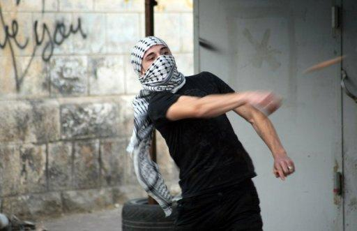 A Palestinian throws stones towards Israeli soldiers guarding the Jewish settlements of Beit Hadasa and Beit Romano during clashes in the Israeli occupied West Bank town of Hebron last month. Israeli Prime Minister Benjamin Netanyahu was due in Berlin on Wednesday for talks likely to focus on the growing crisis over settlement plans that could torpedo the viability of a Palestinian state