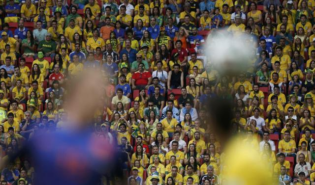 Fans watch as Dirk Kuyt of the Netherlands (L) fights for the ball with Brazil's Oscar during their 2014 World Cup third-place playoff at the Brasilia national stadium in Brasilia July 12, 2014. REUTERS/Ueslei Marcelino (BRAZIL - Tags: SOCCER SPORT WORLD CUP TPX IMAGES OF THE DAY)