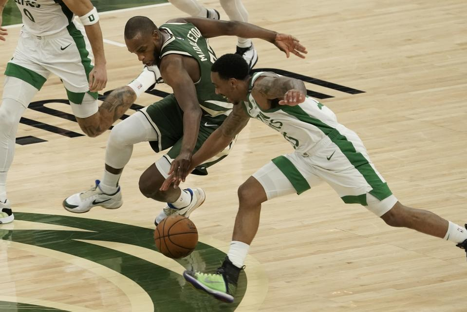 Milwaukee Bucks' Khris Middleton and Boston Celtics' Jeff Teague go after a loose ball during the second half of an NBA basketball game Wednesday, March 24, 2021, in Milwaukee. (AP Photo/Morry Gash)