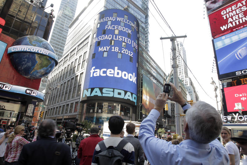 A man stops to photograph Nasdaq in Times Square as Facebook has its IPO, Friday, May 18, 2012, in New York. The social media company priced its IPO on Thursday at $38 per share, and beginning Friday regular investors will have a chance to buy shares. (AP Photo/Richard Drew)