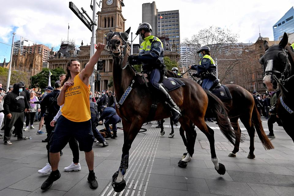 A man appears to hit a horse at Sydney protest.
