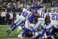 Dallas Cowboys' Keanu Neal (42), Micah Parsons (11) and Jayron Kearse (27) help defend as New York Giants running back Devontae Booker (28) reaches the end zone over the top of the pile for a touchdown in the first half of an NFL football game in Arlington, Texas, Sunday, Oct. 10, 2021. (AP Photo/Michael Ainsworth)