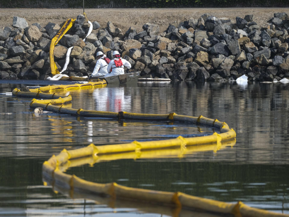 Crews deploy skimmers and floating barriers known as booms to try to stop further incursion into the Wetlands Talbert Marsh in Huntington Beach, Calif., Sunday, Oct. 3, 2021. (AP Photo/Ringo H.W. Chiu)