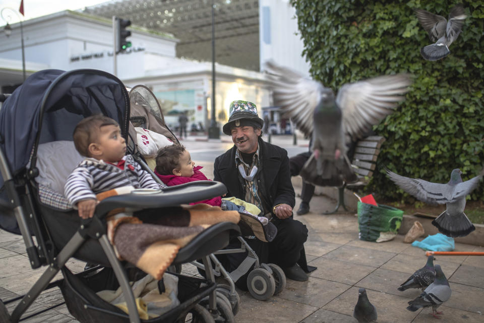 Belhussein Abdelsalam, 58, a Charlie Chaplin impersonator reacts while performing for some children, in an avenue in Rabat, Morocco, Thursday, Dec. 17, 2020. When 58-year-old Moroccan Belhussein Abdelsalam was arrested and lost his job three decades ago, he saw Charlie Chaplin on television and in that moment decided upon a new career: impersonating the British actor and silent movie maker remembered for his Little Tramp character. (AP Photo/Mosa'ab Elshamy)