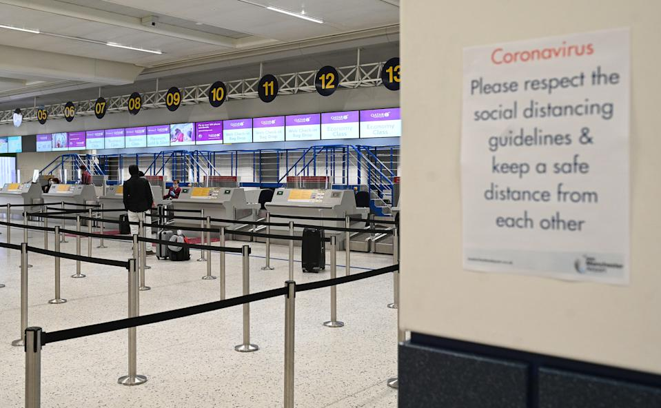 Passengers wearing PPE (personal protective equipment), including a face mask as a precautionary measure against COVID-19, observe social distancing measures as they wait at almost-empty check-in desks in the departure hall at Terminal 1 of Manchester Airport in Manchester, northern England on May 11, 2020, where they have begun a trial of body temperature screening during the COVID-19 pandemic. - Prime Minister Boris Johnson has announced plans to quarantine people arriving in Britain by air for 14 days to prevent new COVID-19 infections from abroad, under a phased lockdown easing that seeks to avoid a second spike. (Photo by Oli SCARFF / AFP) (Photo by OLI SCARFF/AFP via Getty Images)