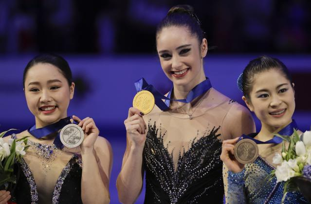 Kaetlyn Osmond of Canada, center, winner of the women's free skating program, shows her gold medal on the podium with second placed Wakaba Higuchi of Japan, left, and third placed Satoko Miyahara of Japan, at the Figure Skating World Championships in Assago, near Milan, Italy, Friday, March 23, 2018. (AP Photo/Luca Bruno)
