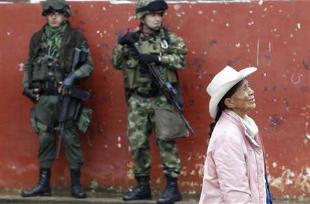 Soldiers stand guard as a woman walks past during a congressional election in Toribio in Cauca province March 9, 2014. REUTERS/Jaime Saldarriaga