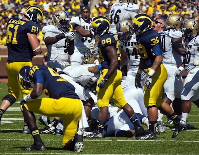 Michigan quarterback Devin Gardner (98) kneels on the field after fumbling the ball as Akron defenders celebrating the recovery in the second quarter of an NCAA college football game, Saturday, Sept. 14, 2013, in Ann Arbor, Mich. (AP Photo/Tony Ding)