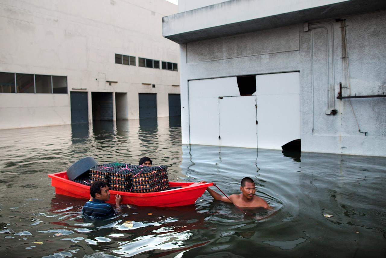 BANGKOK,THAILAND - NOVEMBER 3:  Men pull eggs in a small boat through the floodwater at the closed Don Muang airport November 3, 2011 in Bangkok,Thailand. The airport was used as a domestic terminal and was formerly the International airport. Thailand is experiencing the worst flooding in over 50 years and has affected more than nine million people. Over 400 people have died in flood-related incidents since late July according to the Department of Disaster Prevention and Mitigation.  (Photo by Paula Bronstein/Getty Images)