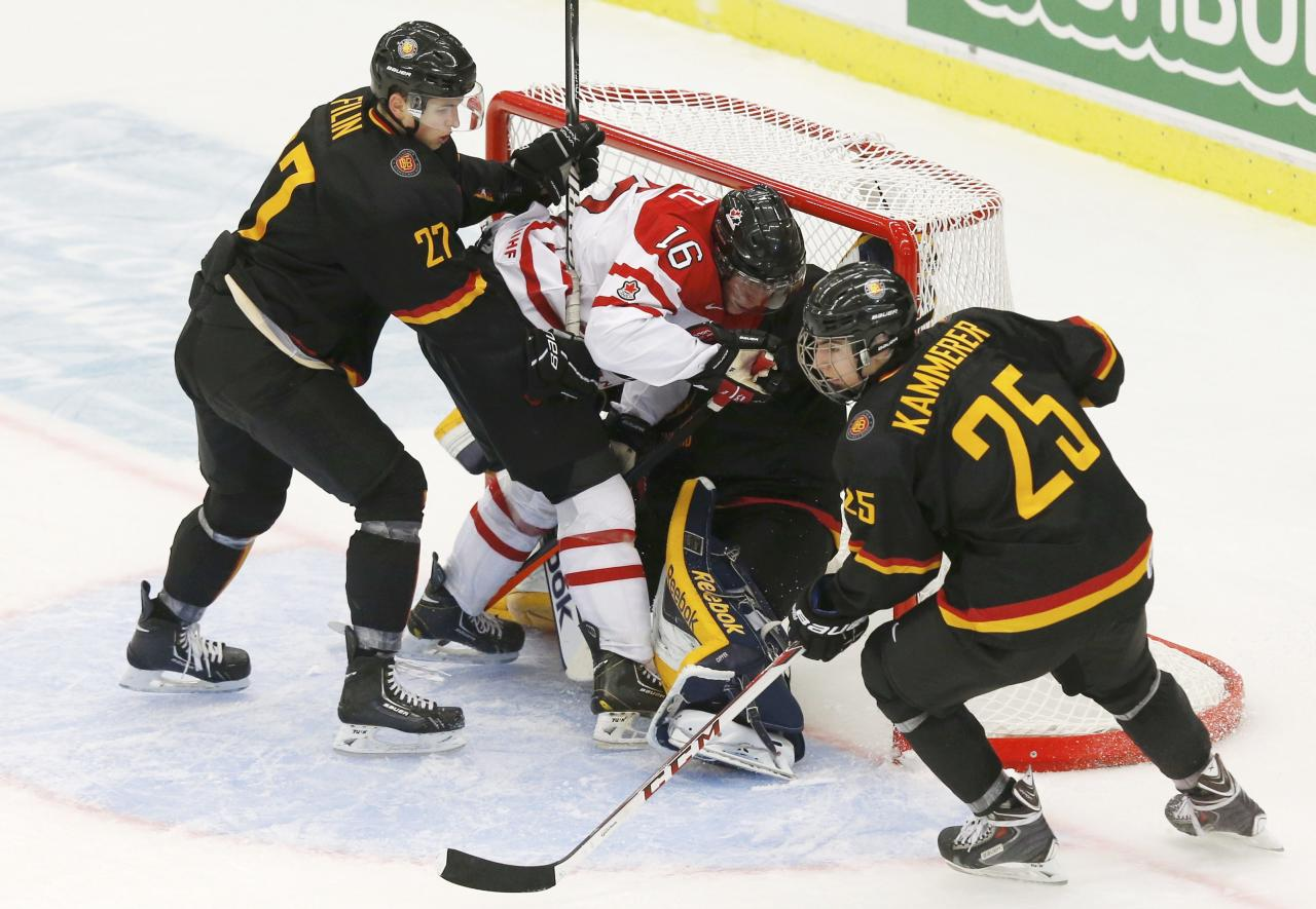 Canada's Kerby Rychel (16) is pushed into Germany's goalie Marvin Cupper by Germany's Vladislav Filin as Germany's Maximilian Kammerer (R) looks on during the third period of their IIHF World Junior Championship ice hockey game in Malmo, Sweden, December 26, 2013. REUTERS/Alexander Demianchuk (SWEDEN - Tags: SPORT ICE HOCKEY)