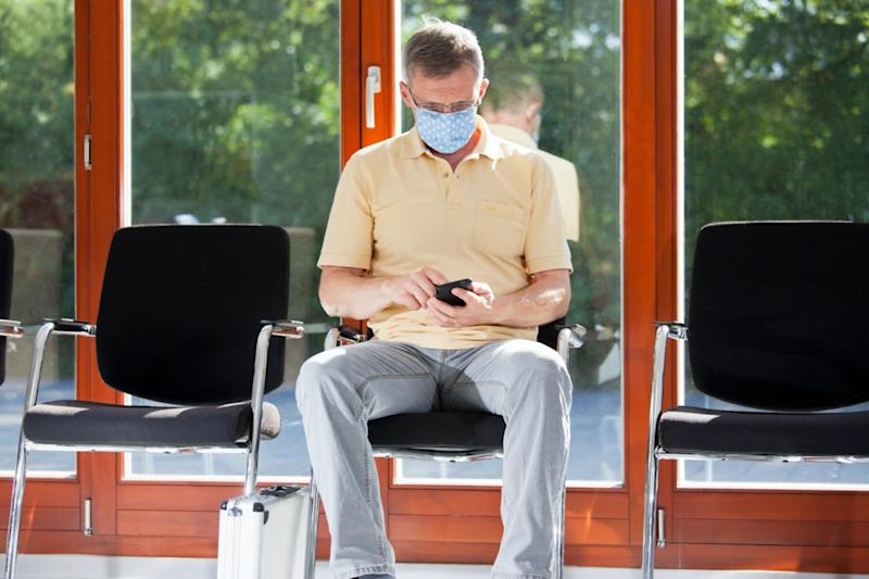 Mature man with face mask sitting in a bright waiting room of a hospital or an office looking at smart phone