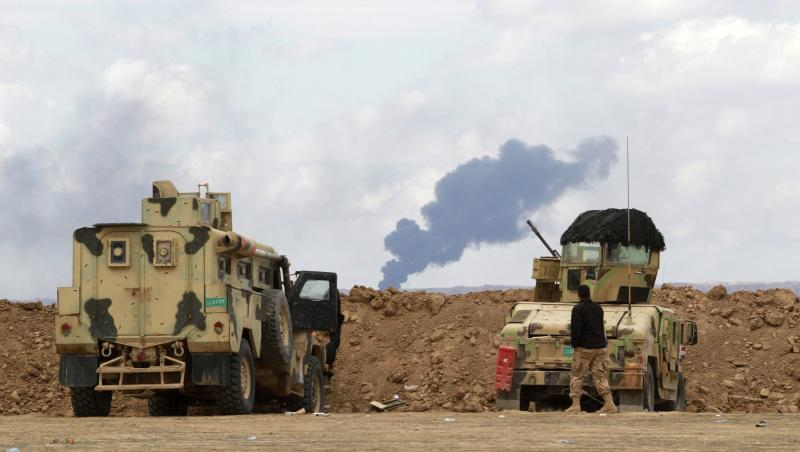 Smoke rises from oil wells in the Ajil field east of the city of Tikrit in the Salahuddin province