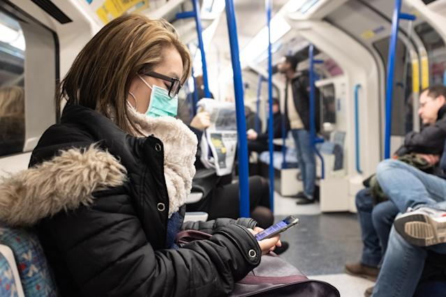A woman wearing a face mask on the London Underground (PA)
