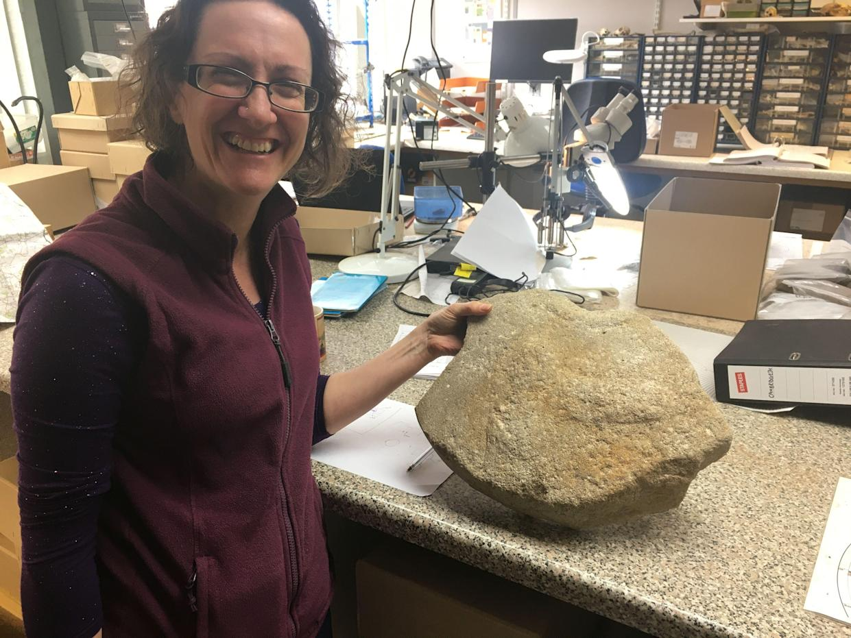 Dr Ruth Shaffrey of Oxford Archaeology with the rare Roman millstone (Highways England/ PA)
