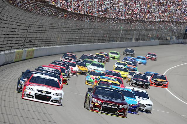 Kevin Harvick, left, and Jeff Gordon, right, lead the start of the NASCAR Quicken Loans 400 auto race at Michigan International Speedway in Brooklyn, Mich., Sunday, June 15, 2014. (AP Photo/Bob Brodbeck)