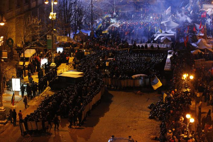 Ukrainian riot police storm Pro-European Union activists gathered in their tent camps on the Independence Square in Kiev, Ukraine, Wednesday, Dec. 11, 2013. Security forces clashed with protesters as they began tearing down opposition barricades and tents set up in the center of the Ukrainian capital early Wednesday, in an escalation of the weeks-long standoff threatening the leadership of President Viktor Yanukovych. (AP Photo/Alexander Zemlianichenko)