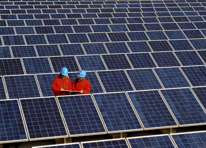 In this Tuesday Feb. 7, 2012 photo, workers check solar panels at a solar power station on a factory roof in Changxing, eastern China's Zhejiang province. The European Union announced Tuesday, June 4, 2013 that it is to impose anti-dumping levies on imports of Chinese solar panels, in a move that could trigger a trade war between two of the world's largest economies. EU Trade Commissioner Karel de Gucht said Tuesday the 27-nation bloc will impose a tariff of about 12 percent on the import of panels, cells and wafers immediately, increasing it to an average of 47 percent starting in August unless a settlement is reached with China. (AP Photo) CHINA OUT