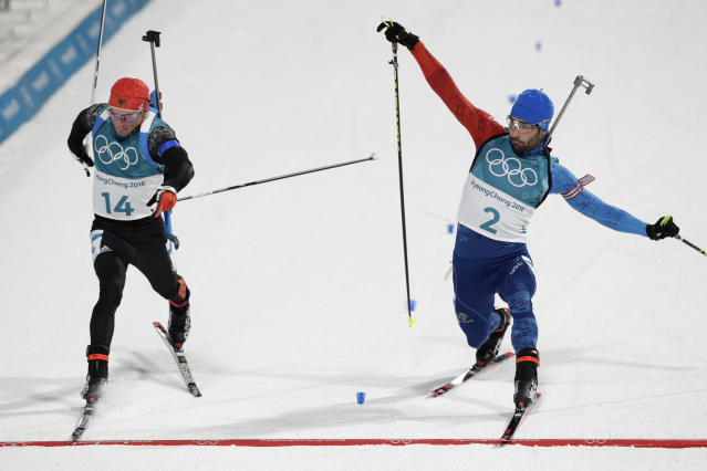 Simon Schempp, of Germany, left, and Martin Fourcade, of France, right, race across the finish line during the men's 15-kilometer mass start biathlon at the 2018 Winter Olympics in Pyeongchang, South Korea, Sunday, Feb. 18, 2018. (AP Photo/Andrew Medichini)