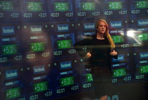 A television anchor stands in front of screens showing the start of trading in Facebook shares at the NASDAQ