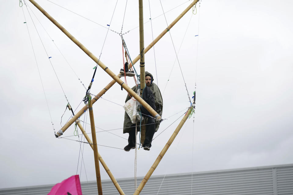 An Animal Rebellion protester suspended from a bamboo structure outside a McDonald's distribution site in Hemel Hempstead, England, Saturday May 22, 2021. Animal rights protesters are blockading four McDonald's distribution centres in the U.K. in an attempt to get the burger chain to commit to becoming fully plant-based by 2025. Animal Rebellion said Saturday that trucks and bamboo structures are being used at the distribution sites in Hemel Hempstead, Basingstoke, Coventry and Heywood, Greater Manchester, to stop lorries from leaving depots. (Yui Mok/PA via AP)