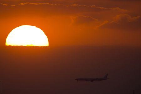 A passenger jet flies past the setting sun in Shanghai