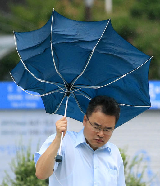 A man holds a damaged umbrella while braving strong winds and rain caused by Typhoon Bolaven in Seoul, South Korea, Tuesday, Aug. 28, 2012. The powerful typhoon pounded South Korea with strong winds and heavy rain Tuesday, while the nation's coast guard battled rough seas in a race to rescue fishermen on two Chinese ships that slammed into rocks off the southern coast. (AP Photo/Lee Jin-man)
