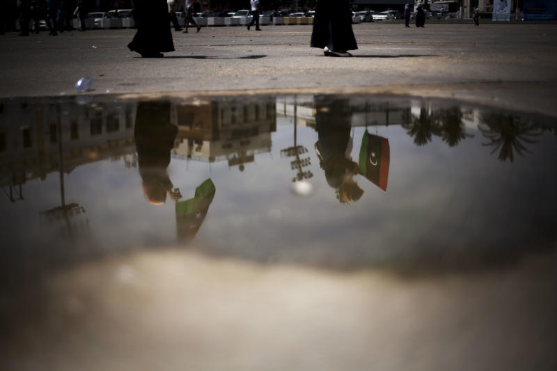 Two Libyan women are reflected in a puddle as they hold national fags during an election day celebration?on in Martyrs' Square in Tripoli, Libya, Saturday, July 7, 2012. Jubilant Libyan voters marked a major step toward democracy after decades of erratic one-man rule, casting their ballots Saturday in the first parliamentary election after last year's overthrow and killing of longtime leader Moammar Gadhafi. But the joy was tempered by boycott calls, the burning of ballots and other violence in the country's restive east. (AP Photo/Manu Brabo)