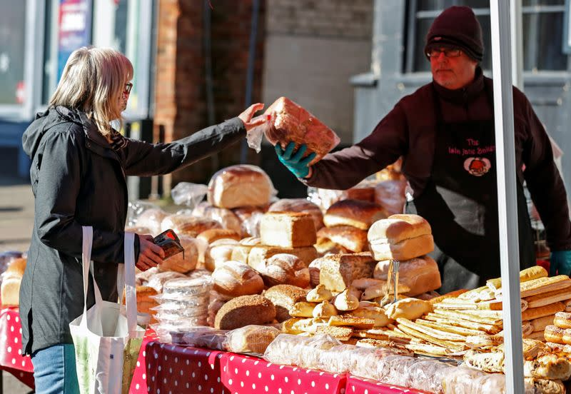 A lady buys bread from a market stall in Buckingham, Britain