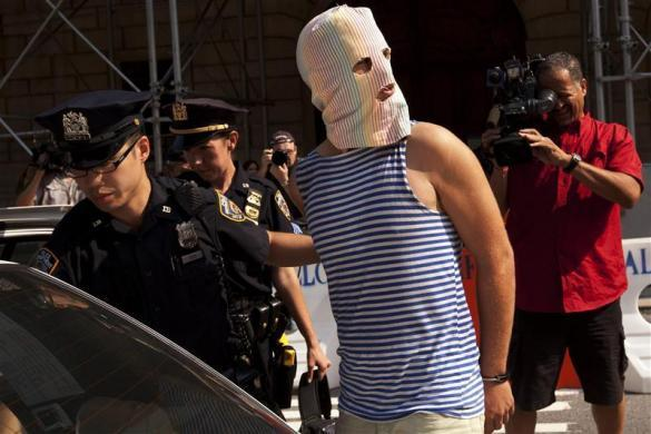 New York Police Department officers arrest a man demonstrating in solidarity with the Russian punk band Pussy Riot in front of the Russian Consulate in New York August 17, 2012.
