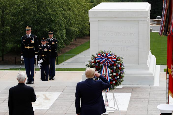 President Donald Trump salutes at the Tomb of the Unknown Soldier in Arlington National Cemetery, in honor of Memorial Day, Monday, May 25, 2020, in Arlington, Va., with Vice President Mike Pence.