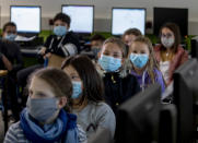 FILE - In this Oct. 21, 2020 file photo, pupils of a fifth class at a high school wear face masks as they take part in an electronic learning session in Frankfurt, Germany. More than 50,000 people have died after contracting COVID-19 in Germany, a number that has risen swiftly over recent weeks as the country has struggled to bring down infection figures. (AP Photo/Michael Probst, File)