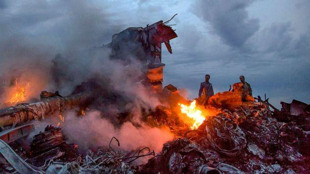 PHOTO: People walk through the debris at the crash site of Malaysia Airlines Flight 17 near the village of Grabove, Ukraine, July 17, 2014. (Dmitry Lovetsky/AP, FILE)