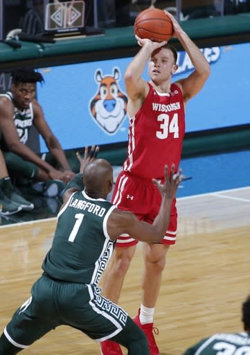 Wisconsin's Brad Davison, right, shoots against Michigan State's Joshua Langford (1) during the first half of an NCAA college basketball game, Friday, Dec. 25, 2020, in East Lansing, Mich. Wisconsin won 85-76. (AP Photo/Al Goldis)