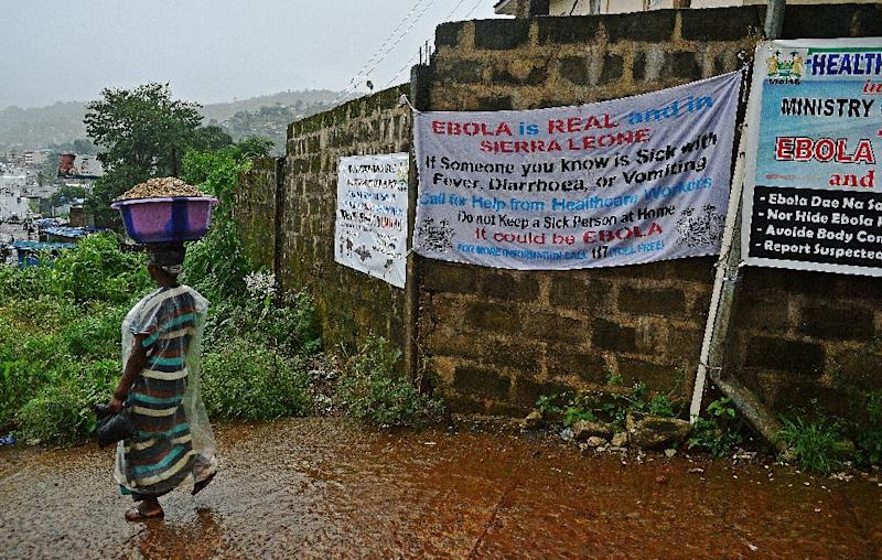 A woman walks past signs warning of Ebola in Freetown, Sierra Leone, on August 13, 2014