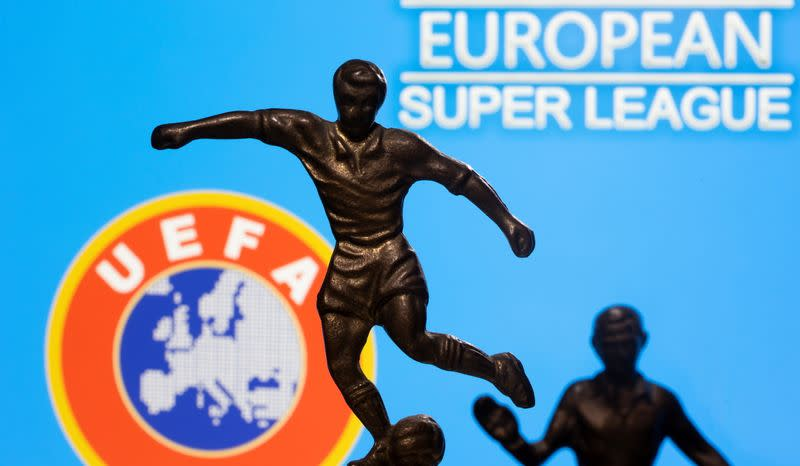 """Metal figures of football players are seen in front of the words """"European Super League"""" and the UEFA logo in this illustration"""