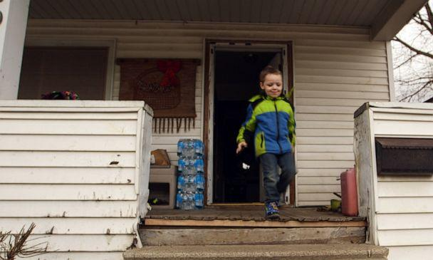PHOTO: Four-year-old Michael Uherek runs to the car as cases of water bottles collected from a distribution center sit outside his family's home in Flint, Mich. (Janet Weinstein/ABC News)