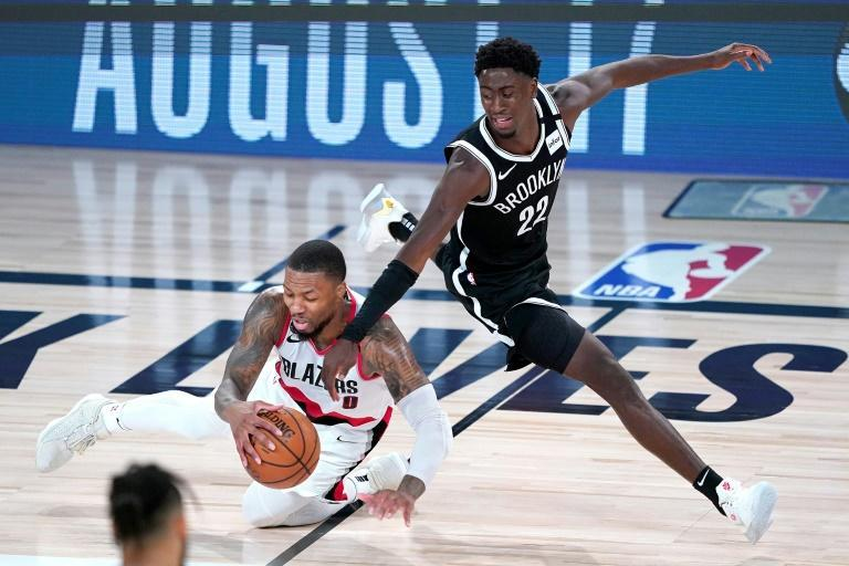 Portland's Damian Lillard falls while chasing the ball against Brooklyn's Caris LeVert in the Trail Blazers' 134-133 NBA victory over the Nets