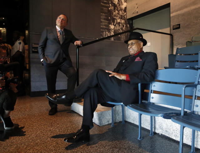 FILE - In this Oct. 3, 2018, file photo, Hockey Hall of Famer Willie O'Ree, right, who was the first African-American hockey player in the NHL, sits briefly in a replica of seats from Ebbets Field, in front of a large photograph of Jackie Robinson's first game, during a tour of the Smithsonian's National Museum of African American History and Culture with NHL commissioner Gary Bettman, left, in Washington. Through his work as the NHLs diversity ambassador over the past 20 years, ORee has tried to work toward more inclusion and better minority representation. (AP Photo/Jacquelyn Martin, File)