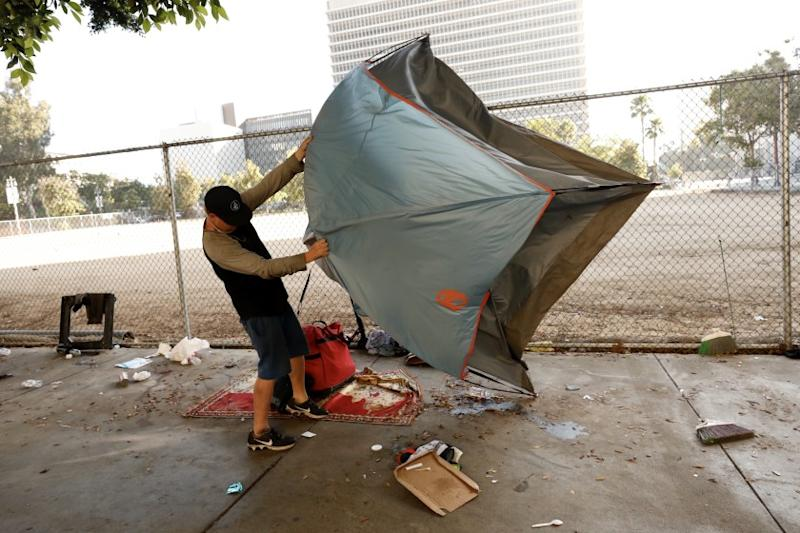 LOS ANGELES CA JULY 1, 2019 -- Homeless people pack up their belongings along First Street between Broadway and Spring Street during a cleanup Monday morning, July 1, 2019. The area targeted on First Street is the sidewalk in front of a fenced-in empty lot next to a portion of Grand Park used for parking during scheduled events. (Al Seib / Los Angeles Times)