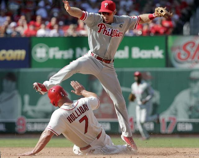 Philadelphia Phillies second baseman Chase Utley leaps to avoid a sliding St. Louis Cardinals' Matt Holliday (7) after forcing him out at second for the front half of a double play in the sixth inning of a baseball game, Saturday, June 21, 2014 in St. Louis. (AP Photo/Tom Gannam)
