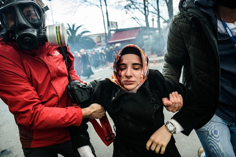 Journalists carry an injured woman after Turkish riot police forcefully dispersed supporters outside the headquarters of the Zaman newspaper in Istanbul on March 5, 2016 (AFP Photo/Ozan Kose)