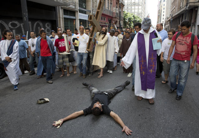 Church volunteers and homeless people participate in a Way of the Cross procession, as a homeless man lies on the ground in downtown Sao Paulo, Brazil, Friday, April 18, 2014. (AP Photo/Andre Penner)