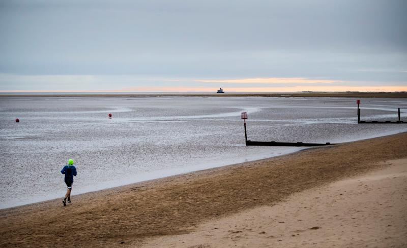 A man jogs in early morning light on the beach at Cleethorpes in North East Lincolnshire.