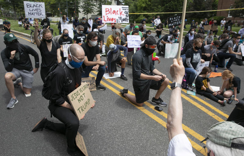 People including Kevin Antlitz, an Anglican priest, left, take a knee during a protest of the visit of President Donald Trump to the Saint John Paul II National Shrine, Tuesday, June 2, 2020, in Washington. Many demonstrators present said they were dismayed when Trump staged a visit to the historic St. John's Church across from the White House and held up a Bible after authorities had cleared the area of peaceful protesters. Protests continue over the death of George Floyd, who died after being restrained by Minneapolis police officers. (AP Photo/Jacquelyn Martin)
