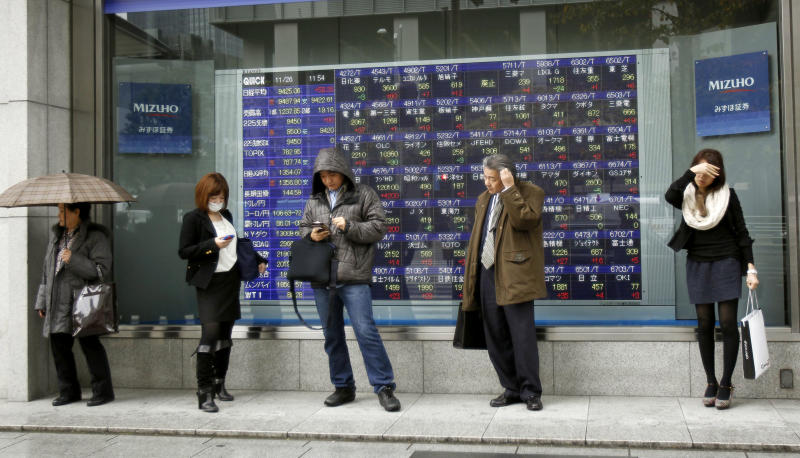 People stand in the rain in front of the electronic stock board of a securities firm in Tokyo, Monday, Nov. 26, 2012. Asian stock markets posted slight gains Monday after the unofficial start of the holiday shopping season in the U.S. topped expectations, offsetting concerns about Greece's financial crisis. (AP Photo/Koji Sasahara)