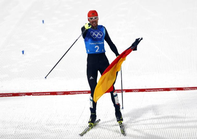 Nordic Combined Events - Pyeongchang 2018 Winter Olympics - Men's Team 4 x 5 km Final - Alpensia Cross-Country Skiing Centre - Pyeongchang, South Korea - February 22, 2018 - Johannes Rydzek of Germany celebrates with the German flag as he approaches the finish line. REUTERS/Dominic Ebenbichler