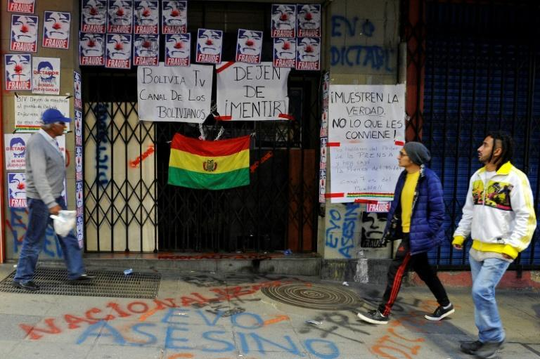 """People walk past the closed entrance of state TV channel BoliviaTV, plastered with pictures depicting President Evo Morales as a clown and calling him a """"fraud"""" on November 9, 2019, in La Paz (AFP Photo/JORGE BERNAL)"""