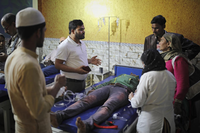 In this Friday, Feb. 28, 2020 photo, Dr. M. A. Anwar, left, speaks to family members of Mehdi Hassan, who was hit by an iron rod by rioters, as he is treated at Al-Hind hospital in Old Mustafabad neighborhood of New Delhi, India. On the eve of U.S. President Donald Trump's first state visit to India last Sunday, Hindus and Muslims in the Indian capital charged at each other with homemade guns and crude weapons, leaving the streets where the rioting occurred resembling a war zone, with houses, shops, mosques, schools and vehicles up in flames, more than 40 dead and hundreds injured. By mid-afternoon Wednesday, Anwar and his overwhelmed colleagues at the clinic had treated more than 400 people, referring almost 100 to larger hospitals. Dozens, however, remained at the clinic in critical condition. More than 50 people rescued from the riots were given refuge inside Al-Hind hospital, aided by an army of volunteers who provided food and bedding. (AP Photo/Altaf Qadri)